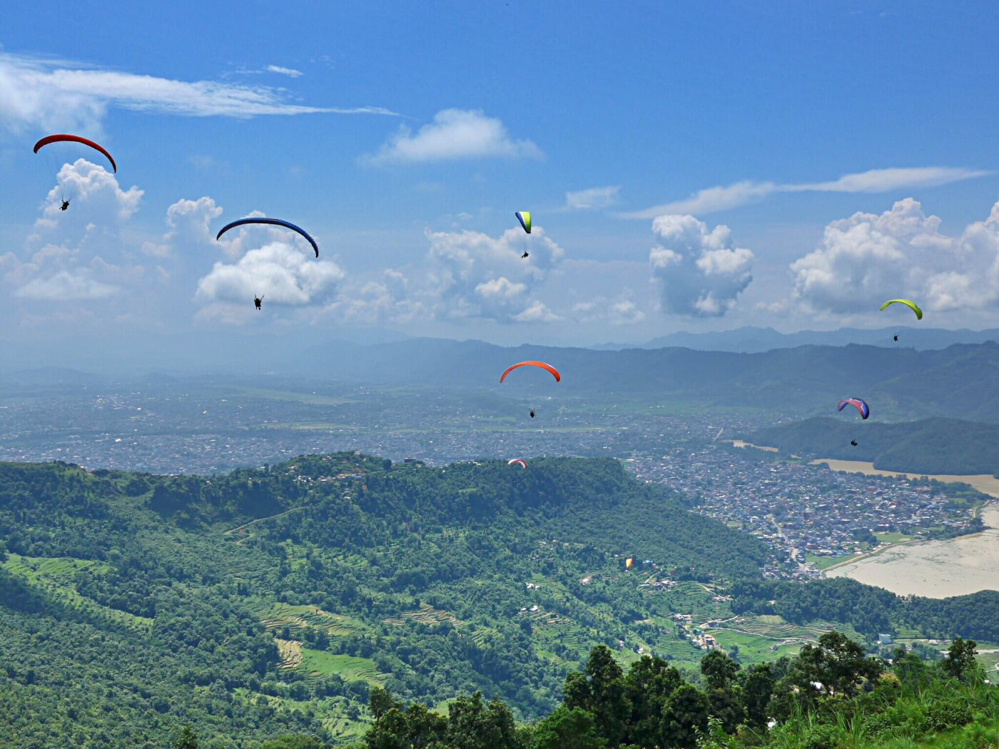 An action shot of my fellow adrenaline junkies paragliding over Pokhara